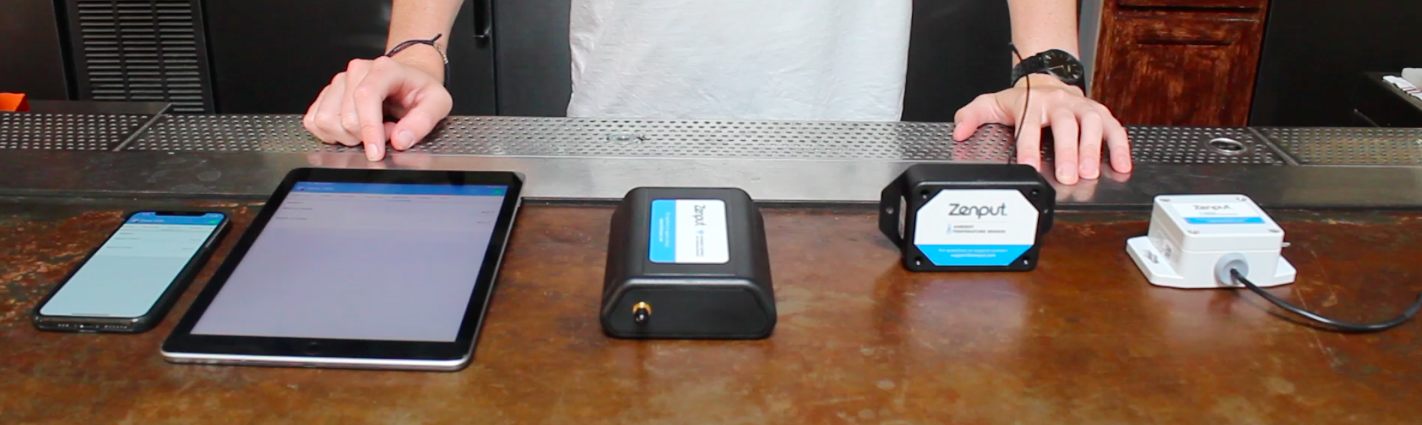 Photo of all devices needed to use Zenput Temp Monitoring, including a gateway, sensor, and smartphone.